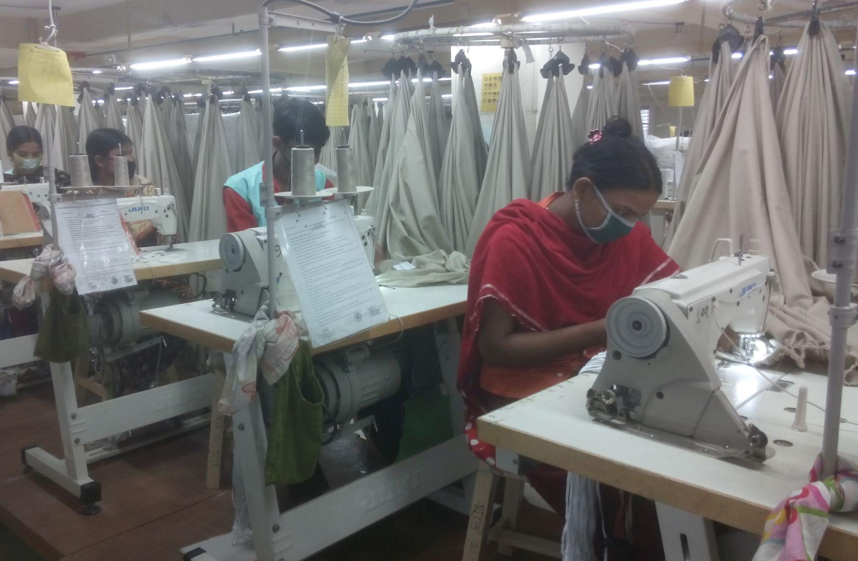 Arbeiterinnen an Nähmaschinen in einer Textilfabrik