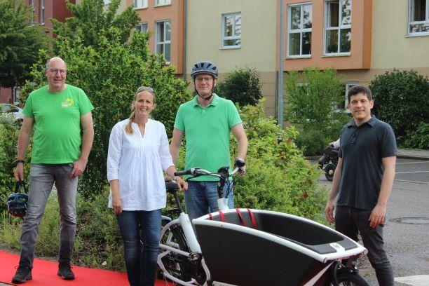 Norbert Knopf MdL, Kristina Steidel, Manuel Steidel und Jürgen Kretz stehen mit einem Lastenrad auf einem roten Teppich