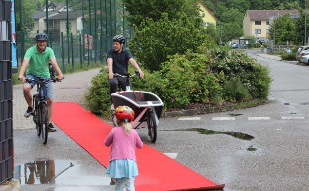 Manuel Steidel und Jürgen Kretz fahren mit Fahrrädern über einen roten Teppich.